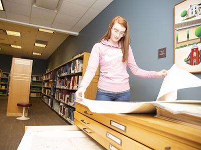 woman looking at maps in genealogy room