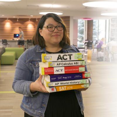Photo os Tenn Services staff member holding large stack of test preparation materials