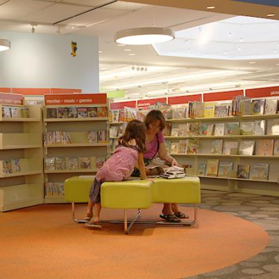Photo of mother and daughter looking at books in the library