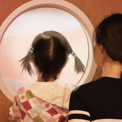 Child and Mother looking through round oindow