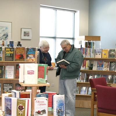 photo of staff and customer in senior center reading room