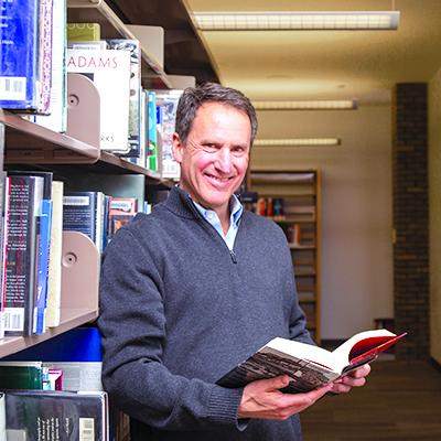 Customer Ken Nopar holding an open book in the library's shelving area