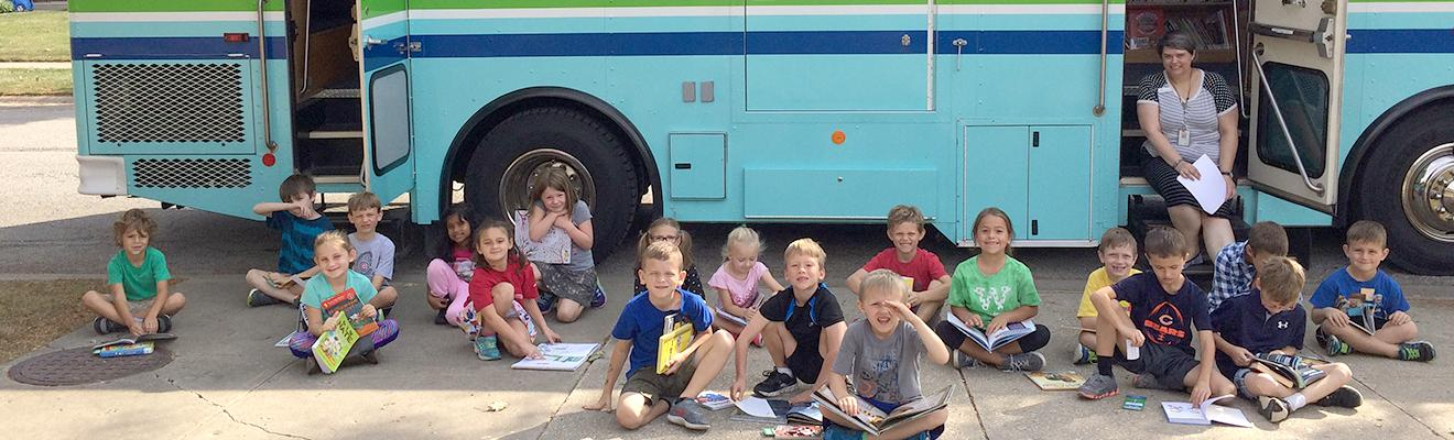 Photo of Bookmobile with kids on sidewalk out front