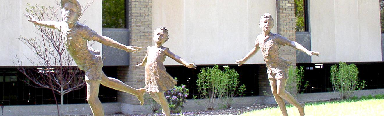 photo of statue outside the library of three children playing