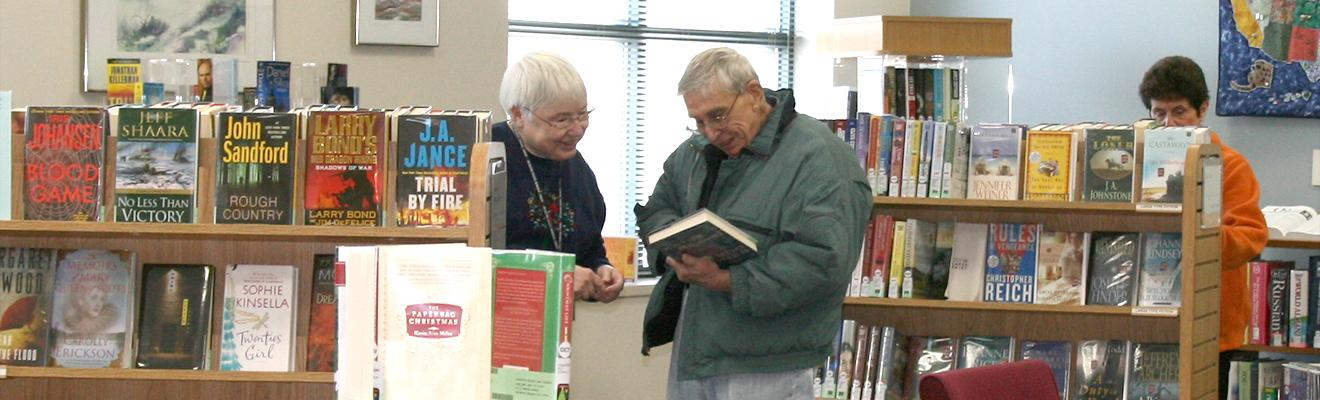 Photo of staff and customer looking at books in the reading room